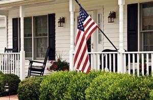 An American flag attached to a house with new vinyl siding