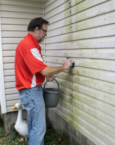 man cleaning vinyl siding