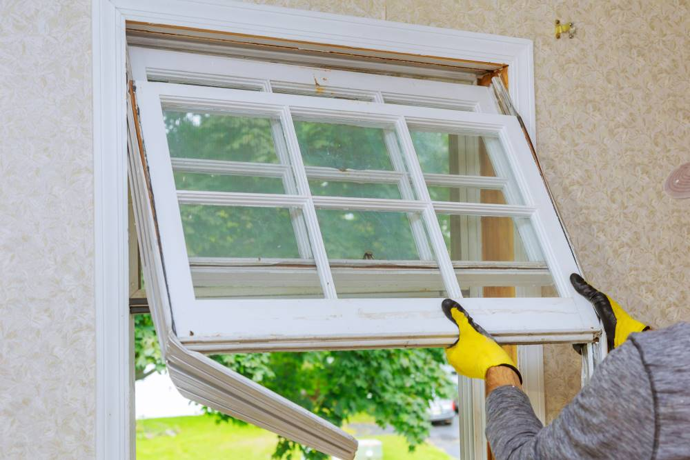 man removing old window